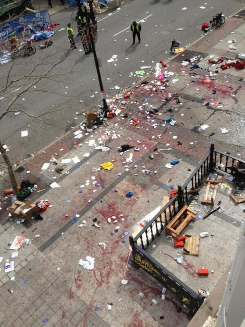 A rua ensanguentada depois do ataque bombista na maratona de Boston que marca o 'Dia dos Patriota', 15 de Abril, 2013